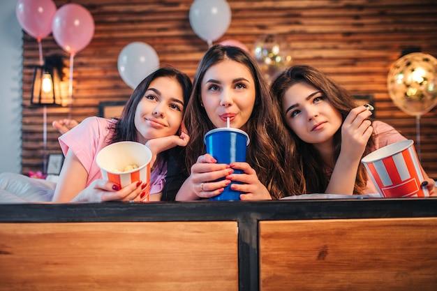 Podekscytowani i kochani nastolatkowie leżący razem na łóżku w świątecznym pokoju. dziewczyna w środku pić colę. pozostałe dwie kobiety mają wiadro z popcornem.