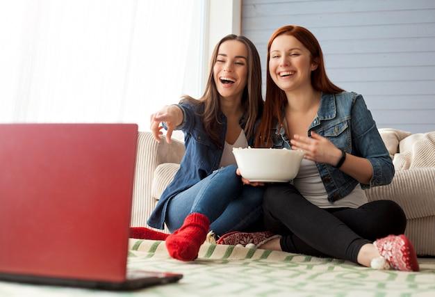 Podekscytowani i szczęśliwi, piękni młodzi przyjaciele oglądają telewizję i jedzą popcorn