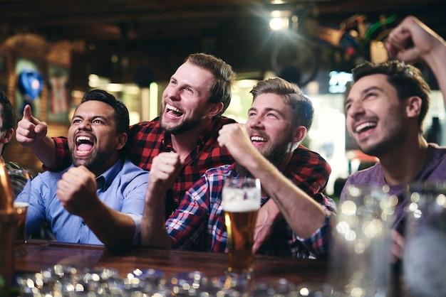 Podekscytowani kibice oglądający piłkę nożną w pubie