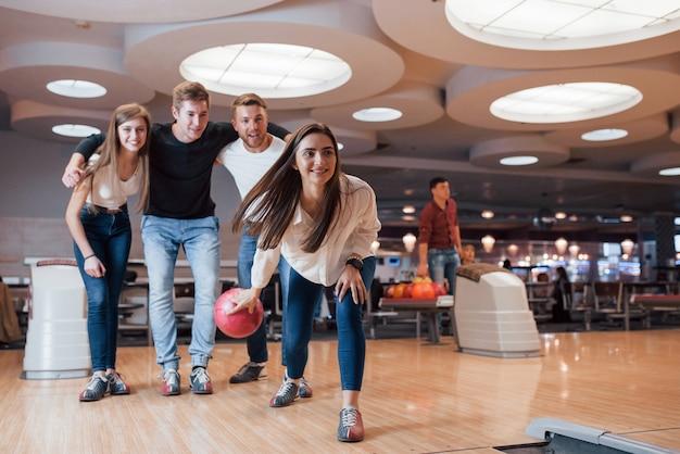 Podekscytowani ludzie. młodzi weseli przyjaciele bawią się w weekendy w kręgielni