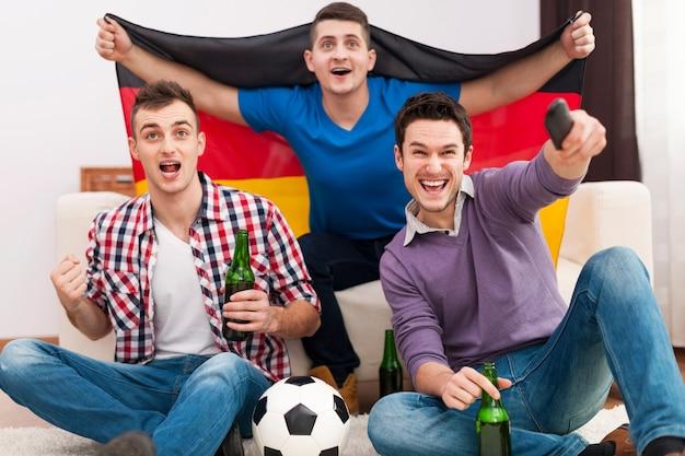 Podekscytowani mężczyźni dopingujący mecz piłki nożnej
