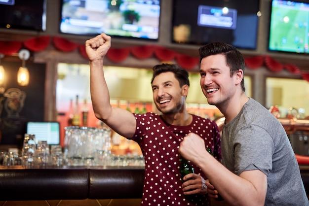 Podekscytowani mężczyźni oglądają zawody futbolu amerykańskiego