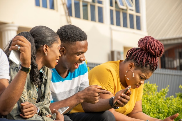 Podekscytowani młodzi afrykańczycy czują się podekscytowani, patrząc na telefon komórkowy, siedząc z przyjaciółmi