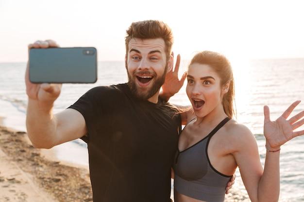 Podekscytowani młodzi kochający przyjaciele para robią selfie przez telefon komórkowy.