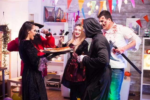Podekscytowani młodzi ludzie o smacznej pizzy na imprezie z okazji halloween.