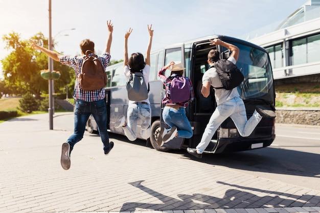 Podekscytowani młodzi ludzie skaczą w pobliżu autobusu turystycznego.