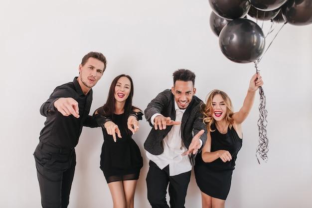 Podekscytowani przyjaciele bawią się na imprezie i wskazują palcem do przodu