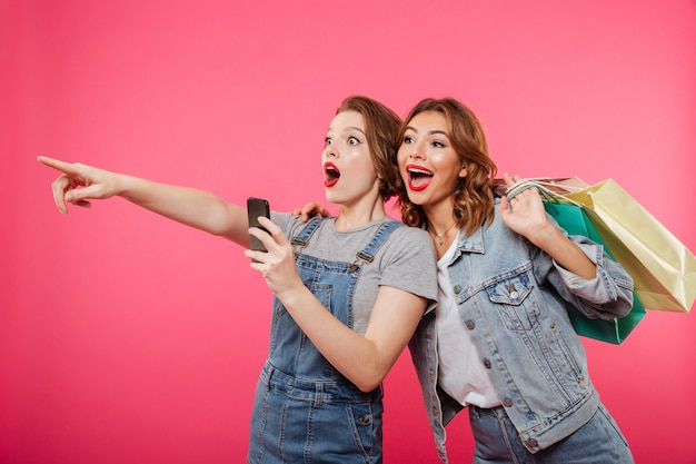 Podekscytowani przyjaciele dwóch kobiet trzymających torby na zakupy za pomocą telefonu komórkowego.