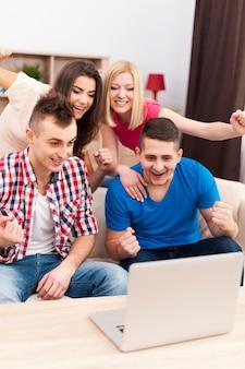 Podekscytowani przyjaciele oglądają mecz piłki nożnej na laptopie