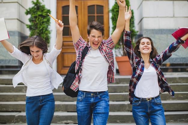 Podekscytowani studenci wychodzący z uniwersytetu