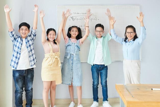 Podekscytowani szczęśliwi azjatyccy uczniowie i ich nauczyciel przedmiotów ścisłych stoją przed tablicą z równaniami, podnoszą ręce i świętują zakończenie trudnego tematu matematycznego