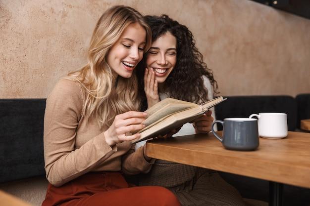 Podekscytowani szczęśliwi ładni przyjaciele dziewczyny siedzą w kawiarni pijąc kawę czytając książkę