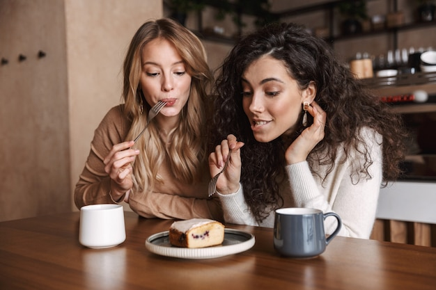 Podekscytowani szczęśliwi ładni przyjaciele dziewczyny siedzą w kawiarni pijąc kawę jedzą ciasto
