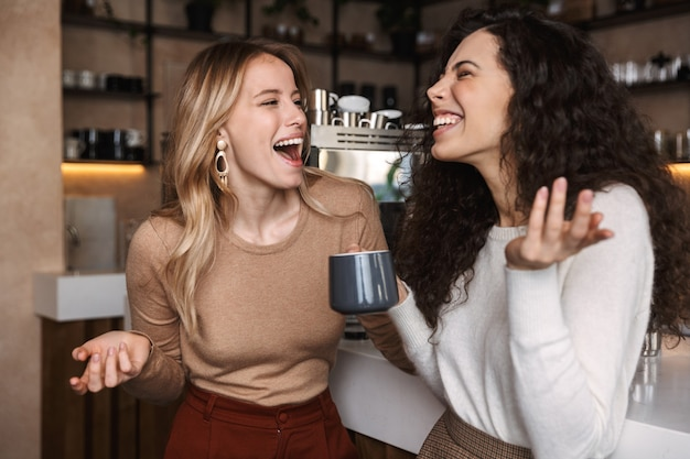 Podekscytowani szczęśliwi ładni przyjaciele dziewczyny siedzą w kawiarni pijąc kawę