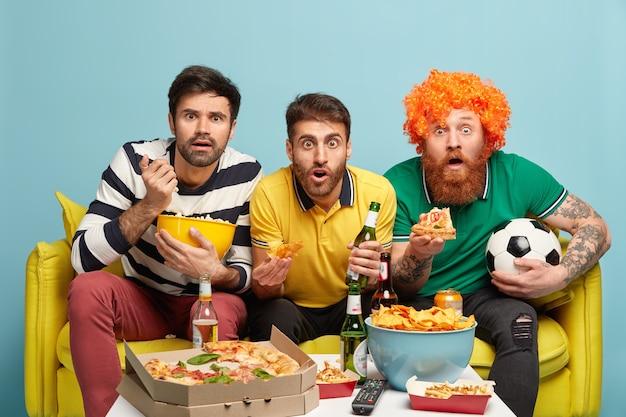 Podekscytowani trzej przyjaciele oglądają zawody sportowe, wstrzymują oddech w niebezpiecznych chwilach, gryzą chipsy, popcorn i pizzę, siedzą na żółtej sofie w salonie. fani piłki nożnej z piwem. kibic piłki nożnej