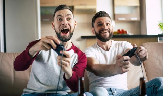 Podekscytowani uśmiechnięci mężczyźni grający w gry wideo w telewizji w domu na kanapie. przyjaciele z joystickami grają w grę ze szczęśliwymi emocjami na twarzach