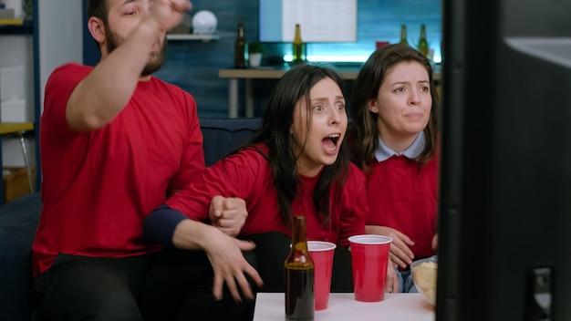 Podekscytowani wieloetniczni fani bawiący się podczas oglądania meczu piłki nożnej w telewizji. szczęśliwi przyjaciele wiwatujący razem po wygraniu mistrzostwa przez drużynę piłkarską, siedząc na kanapie późno w nocy w salonie