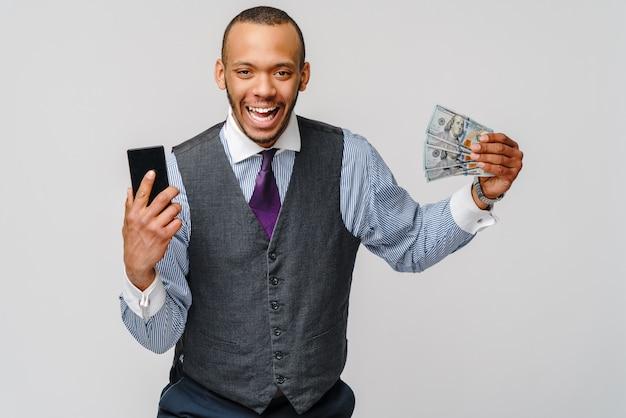 Podekscytowany african american młody biznesmen pokazując banknoty pieniądze i telefon komórkowy