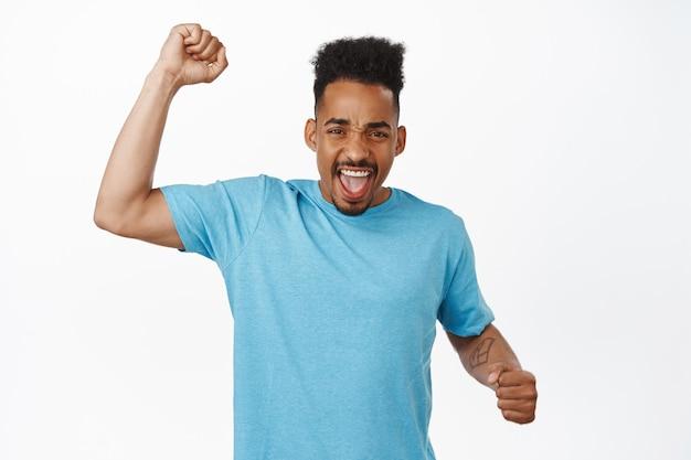 Podekscytowany afroamerykański fan futbolu, facet krzyczy i skanduje, podnosi pięść do góry, krzyczy aktywista, walczy o prawa człowieka na paradzie, kibicuje drużynie, noś niebieską koszulkę na białym backgorund.