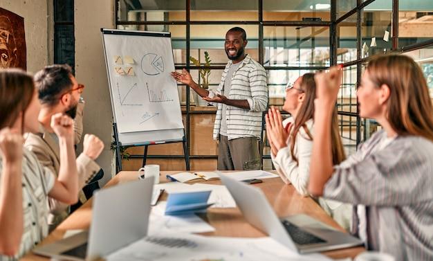 Podekscytowany afrykański i kaukaski zespół biznesowy, motywowany zwycięstwem, osiągnięciami lub dobrymi wynikami, międzynarodowa grupa pracowników wspólnie świętuje sukces korporacji.