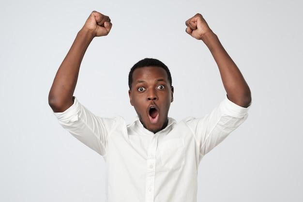 Podekscytowany afrykański mężczyzna z szczęśliwy wyraz twarzy trzyma pięści do góry