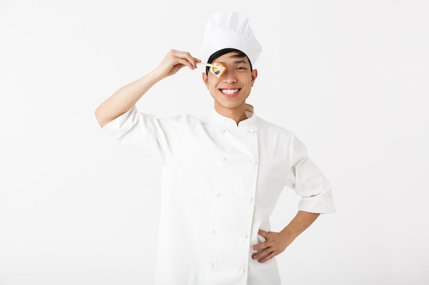 Podekscytowany azjatycki kucharz ubrany w mundur stojący na białym tle nad białą ścianą, przygotowując sushi