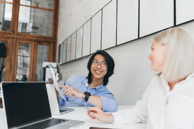 Podekscytowany azjatycki menadżer pokazuje blondynce dokumenty. kryty portret jasnowłosej studentki siedzącej z laptopem rozmawia z chińskim przyjacielem w okularach.