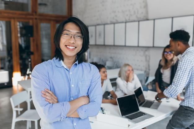 Podekscytowany azjatycki młody człowiek w stylowych okularach stojący z rękami skrzyżowanymi w bibliotece, podczas gdy jego przyjaciele mówią. zadowolony zagraniczny student zdał wszystkie egzaminy i cieszy się z tego.
