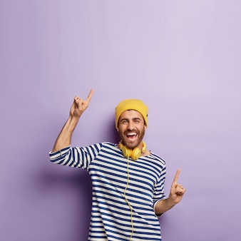 Podekscytowany, beztroski, pozytywny mężczyzna w swobodnym swetrze w paski, żółtym kapeluszu, radośnie wskazuje na niesamowite miejsce na kopię twojej promocji