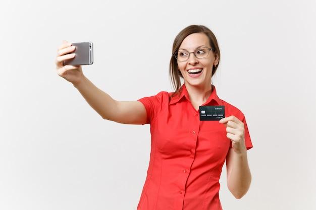 Podekscytowany biznes kobieta w czerwonej koszuli robi biorąc selfie strzał na telefon komórkowy z karty kredytowej, bezgotówkowe pieniądze na białym tle. nauczanie edukacji w koncepcji uniwersytetu liceum.