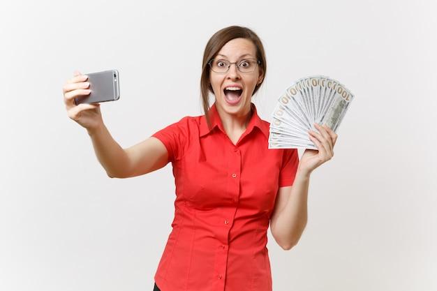 Podekscytowany biznes kobieta w czerwonej koszuli robi biorąc selfie strzał na telefon komórkowy z pakietem wiele dolarów, pieniądze w gotówce na białym tle. nauczanie edukacji w koncepcji uniwersytetu liceum.