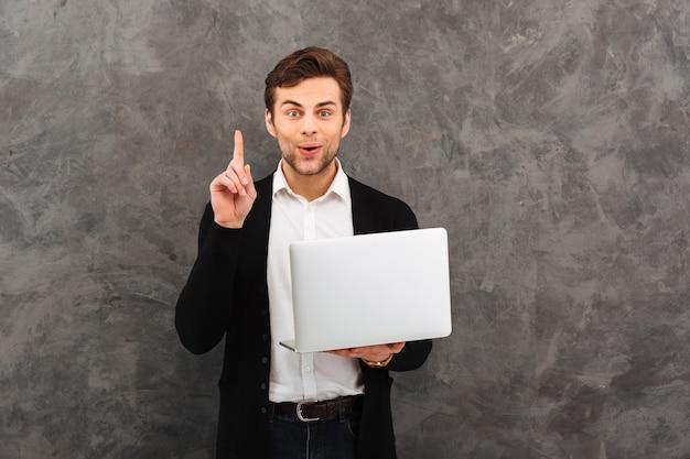 Podekscytowany biznesmen ma pomysł za pomocą laptopa.
