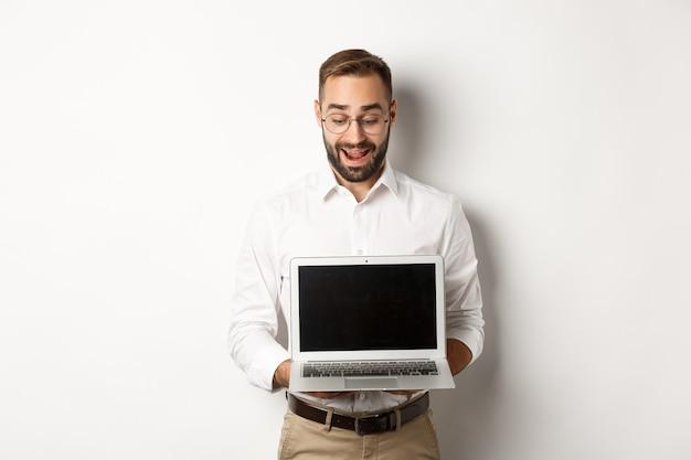 Podekscytowany biznesmen pokazuje coś na ekranie laptopa, stoi szczęśliwy