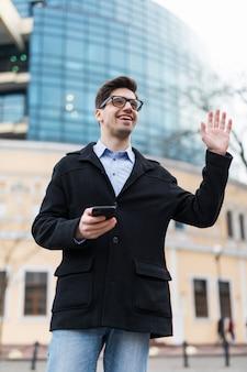 Podekscytowany biznesmen pozdrowienia swojego przyjaciela gestem ręki i trzymając w ręku telefon komórkowy
