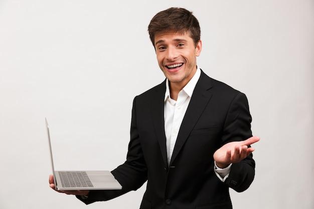 Podekscytowany biznesmen stojący na białym tle przy użyciu komputera przenośnego.