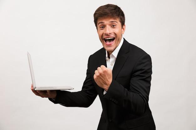 Podekscytowany biznesmen stojący na białym tle za pomocą komputera przenośnego zrobić gest zwycięzcy.