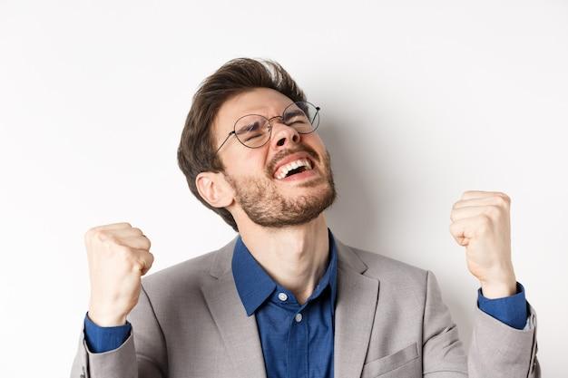 Podekscytowany biznesmen w okularach i garniturze krzyczy z przyjemnością i ulgą tak, ściskając pięści, triumfując, wygrywając zakład, stojąc na białym tle.