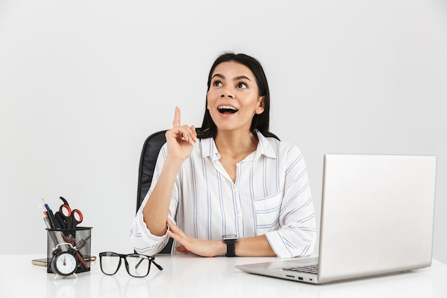Podekscytowany bizneswoman brunetka siedzi przy stole z papeterii i pracy na laptopie w biurze odizolowane na białej ścianie