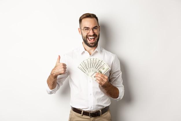 Podekscytowany bogacz trzymający pieniądze, pokazujący kciuk w górę z aprobatą, stojący na białym tle