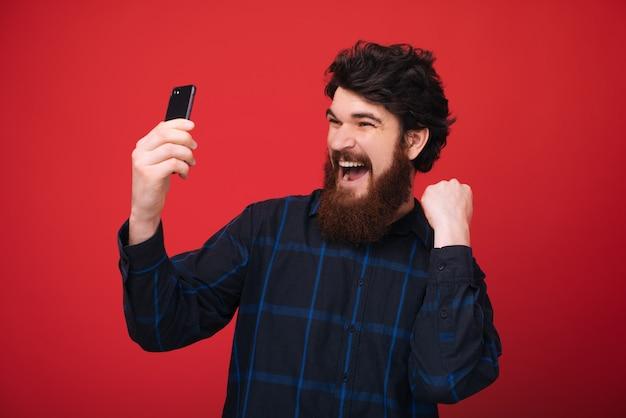 Podekscytowany brodaty facet trzyma telefon i świętuje z podniesioną ręką nad czerwoną ścianą