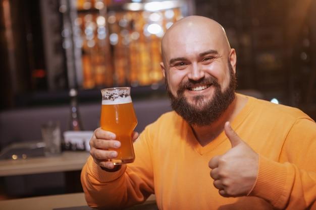 Podekscytowany brodaty łysy mężczyzna uśmiecha się do kamery, pokazując kciuk do góry, popijając szklankę pysznego piwa w pubie