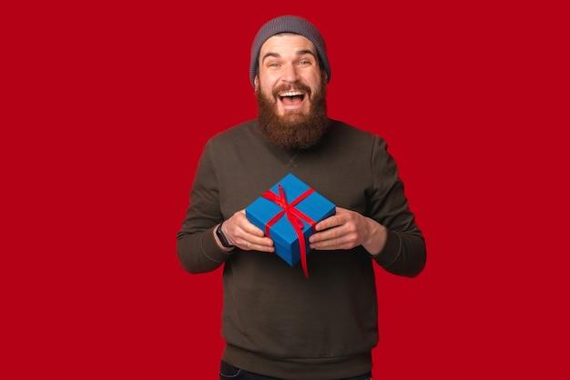 Podekscytowany brodaty mężczyzna trzyma dla ciebie niebieskie pudełko.