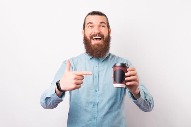 Podekscytowany brodaty mężczyzna wskazuje na papierową filiżankę kawy, którą trzyma.
