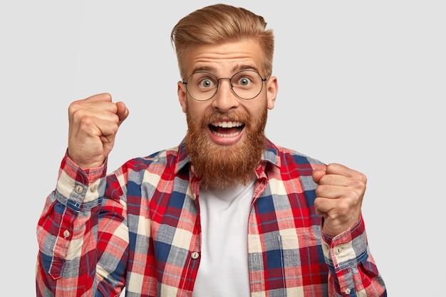 Podekscytowany brodaty młody rudy mężczyzna ma radosny wyraz twarzy, zaciska pięści, będąc w dobrym nastroju, świętując swoje zwycięstwo