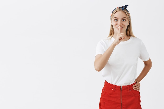 Podekscytowany całkiem młoda blond dziewczyna pozuje na białej ścianie