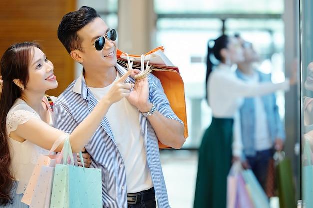 Podekscytowany całkiem młoda kobieta azji z torbą na zakupy pokazując element odzieży w oknie sklepu do swojego uśmiechniętego chłopaka