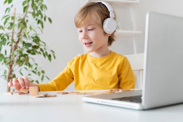 Podekscytowany chłopiec za pomocą laptopa i słuchawek w domu