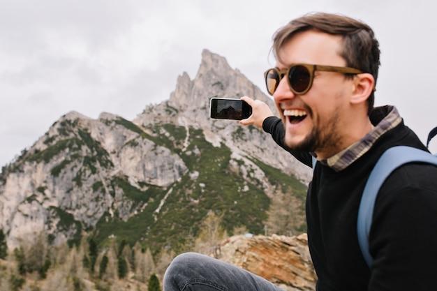 Podekscytowany ciemnowłosy mężczyzna w okularach przeciwsłonecznych odpoczywa w górach po długiej wspinaczce i szczerym śmiechu