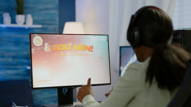 Podekscytowany czarny gracz e-sportu świętujący zwycięstwo w mistrzostwach, kobieta wygrywająca kosmiczną strzelankę. profesjonalne turnieje online w grach cybernetycznych na żywo mistrzostwa na żywo przy użyciu potężnego komputera rgb
