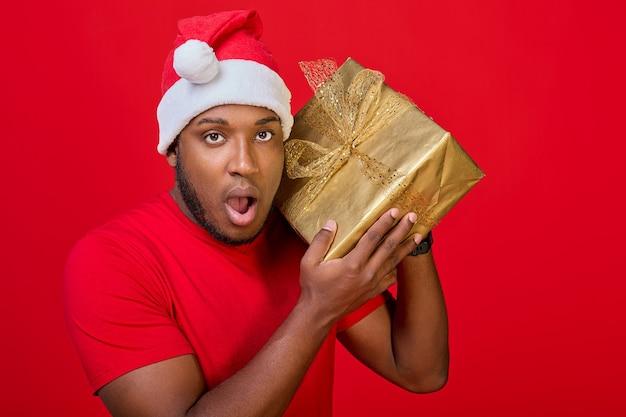 Podekscytowany czarny mężczyzna w czapce świętego mikołaja, potrząsający zapakowanym pudełkiem prezentowym, zastanawiający się, co jest w środku